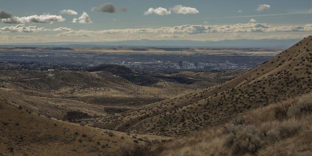 Широкий выстрел из горы покрыты деревьями с городских зданий на расстоянии под голубым облачным небом