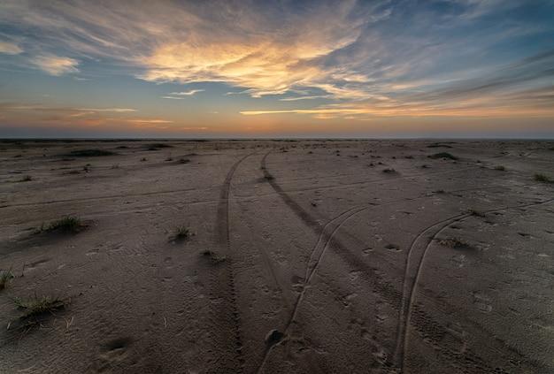 Красивый закат на пляже, создающий идеальный пейзаж для вечерних прогулок на берегу