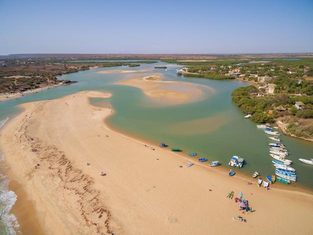 セネガルの青い空の下でクルーズ船と緑に囲まれたビーチのハイショット