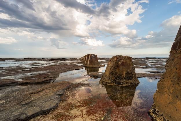 曇り空の下で海の水に囲まれた茶色の岩の美しいショット