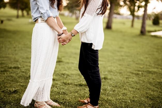 芝生のフィールドに立って手を繋いでいる女性のカップルのクローズアップショット