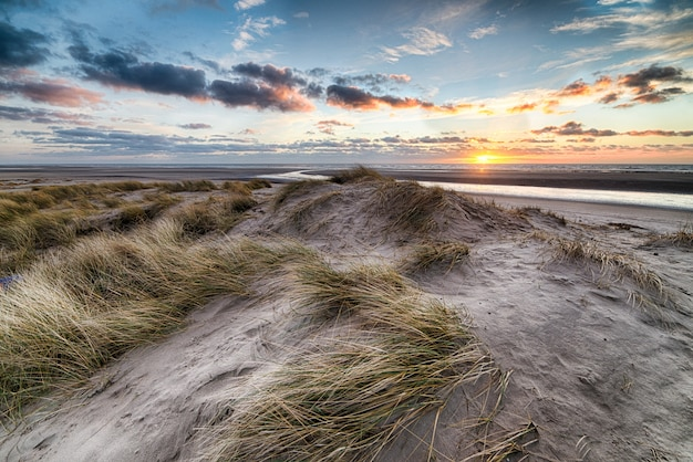 ビーチの美しい日の出は、海岸での朝の散歩に最適な風景を作り出します