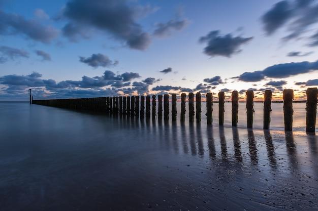 オランダ、ゼーラント州のウエストカペレの海の桟橋に沈む夕日の息をのむような風景