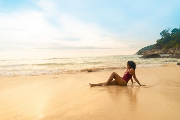 ビーチに座っている赤い水着を着ているモデルのクローズアップショット
