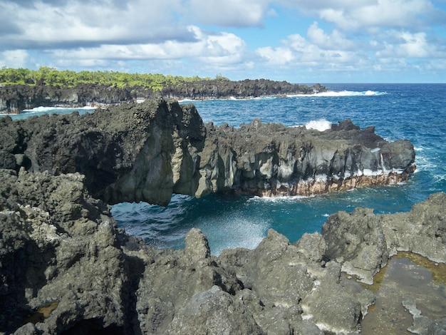 ハワイの曇り空の下のビーチで鋭い岩の美しい風景