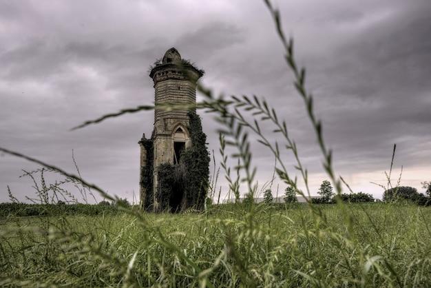 憂鬱な空の下でフィールドの真ん中にある古代の建物のローアングルショット