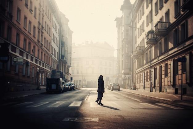 ポーランドで捕らえられた古い建物に囲まれたポズナンの通りの真ん中にいる人