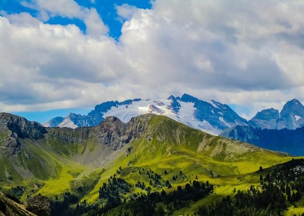 Захватывающий вид на красивые травянистые поля и горы под облаками в небе