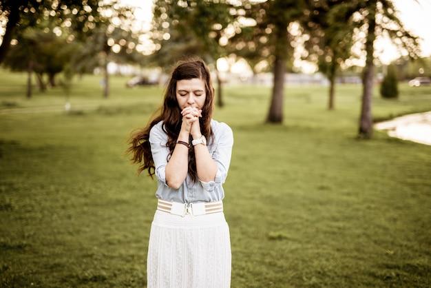背景をぼかした写真で祈りながら彼女の口の近くの彼女の手で女性の美しいショット