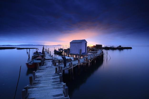木製の桟橋と夕暮れの穏やかな海の上のコテージの息をのむような眺め
