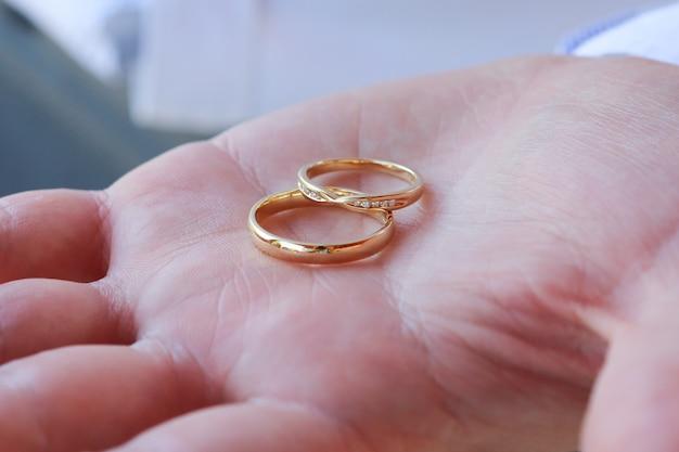 Снимок крупным планом человека, держащего два золотых обручальных кольца