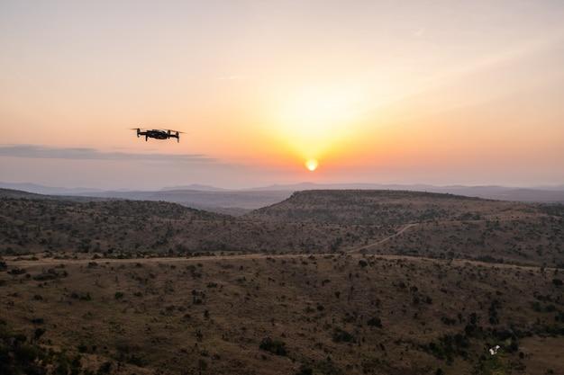 ケニア、ナイロビ、サンブルで美しい夕日と丘の上を飛んでいるドローン