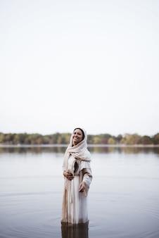 水に立って、笑顔で聖書のローブを着ている女性