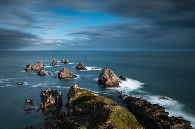 青い曇り空の下で水に大きな岩のある海