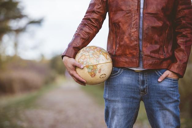 背景をぼかした写真の地球を保持している革のジャケットを着ている男性のクローズアップショット