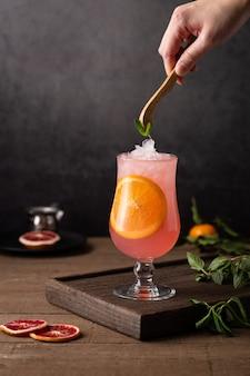 オレンジスライスが入ったグレープフルーツカクテルのグラス