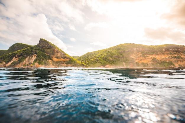 Захватывающий вид на океан и скалы, покрытые растениями, захваченными в ломбок, индонезия