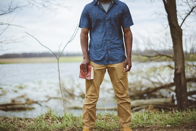 立っている間、聖書を持っている男性のクローズアップショット