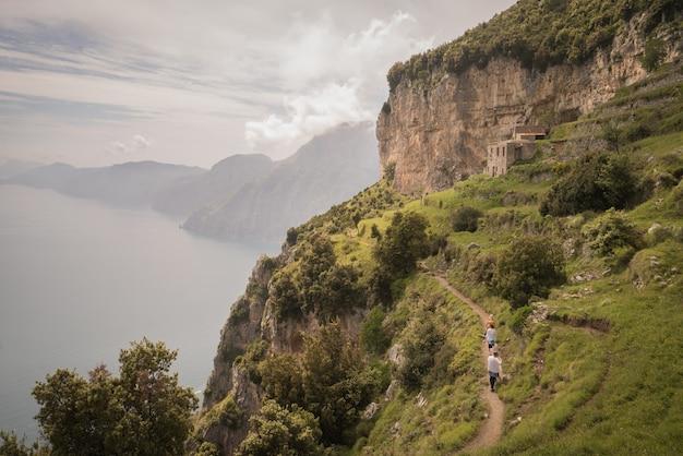 イタリアのアマルフィ海岸で捕獲された海の崖に覆われた草の息をのむような眺め