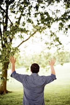 Вертикальный снимок сзади мужчины с поднятыми вверх руками к небу