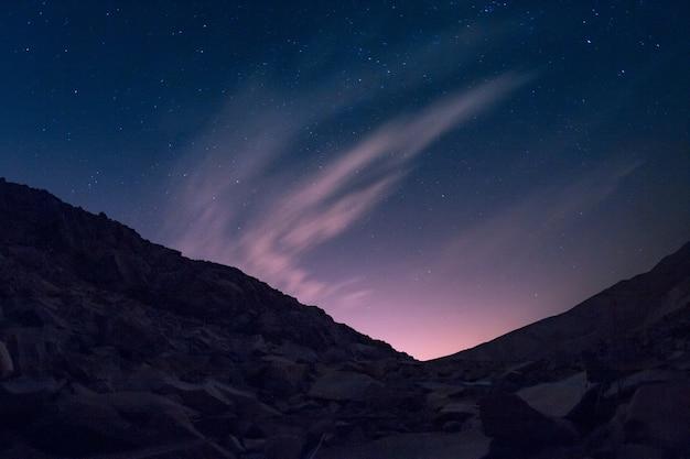 オーロラの美しい星空の下に金属片がたくさんある丘