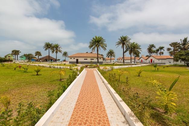 Красивый тротуар и дома в окружении травянистых полей, захваченных в гамбии, африка
