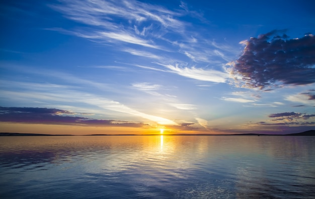 背景の青い空に輝く太陽と海の美しい景色