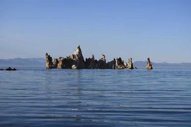 澄んだ空の下、海の真ん中にある岩の美しいショット