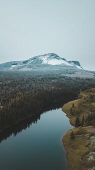 雪に覆われた山、川の後ろ