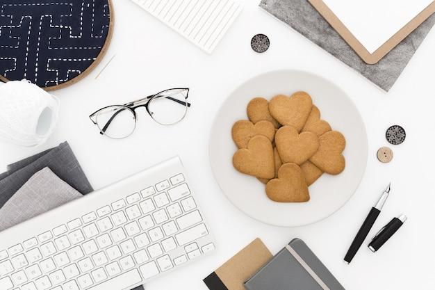キーボード、クッキーのプレート、グラス、および白い表面上のいくつかのペーパーのハイアングルショット