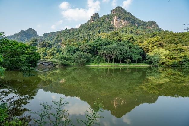 湖に映る緑の木々と高い山々の美しい風景