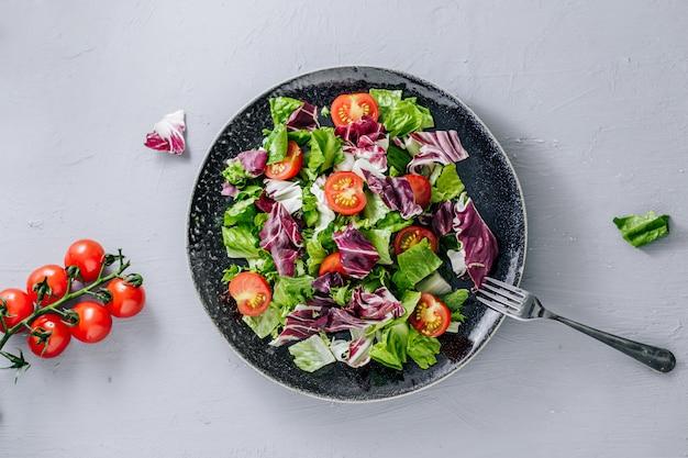 Смешать полезный салат ромейн, мангольд, шпинат с помидорами