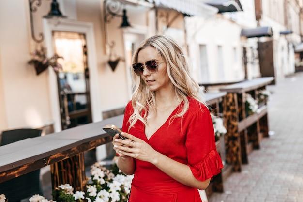 赤いドレスを着た美しいブロンドの女性は、ストリートカフェの近くのスマートフォンを使用しています