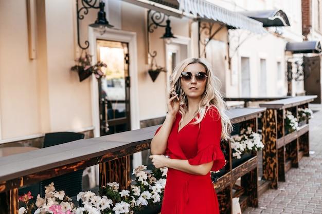 サングラスとストリートカフェの近くに電話で話している赤いドレスを着た美しい女性