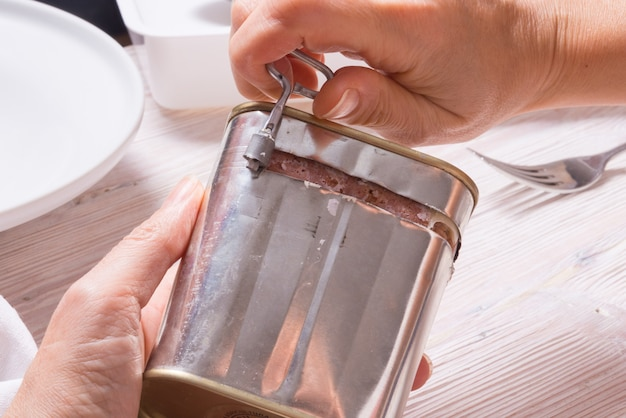 Женщина руки открывая консервную банку с солониной, вид сверху кухонный стол