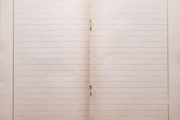 ステープル、織り目加工の背景を持つ古いビンテージ定規ノート