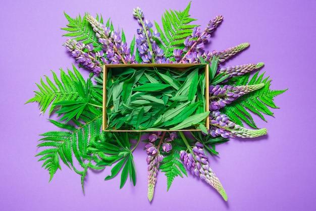 、紫色の背景、上面にルピナスの花で飾られた段ボール箱