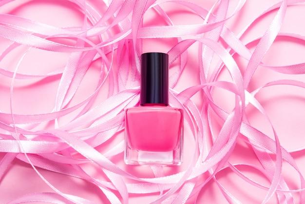 Бутылка лака для ногтей на розовом столе украшена розовой ленточкой
