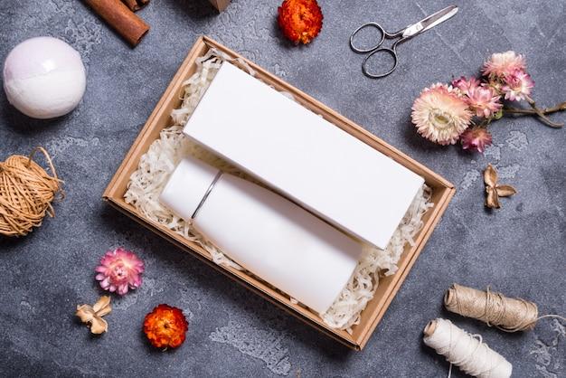 Макет, крем бутылка и картонная коробка на сером фоне