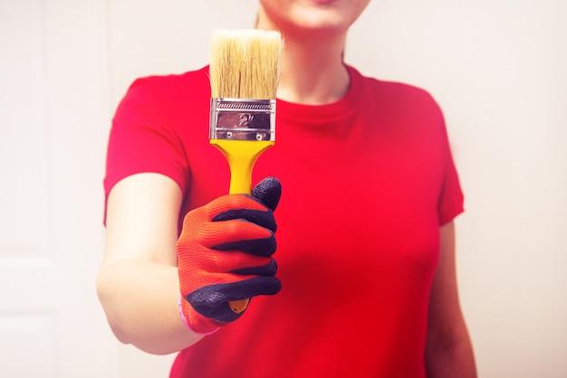 Женщина держит кисть, начиная ремонт дома