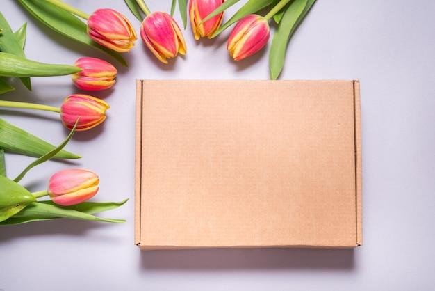 Коричневая картонная коробка и цветы тюльпана на сером фоне