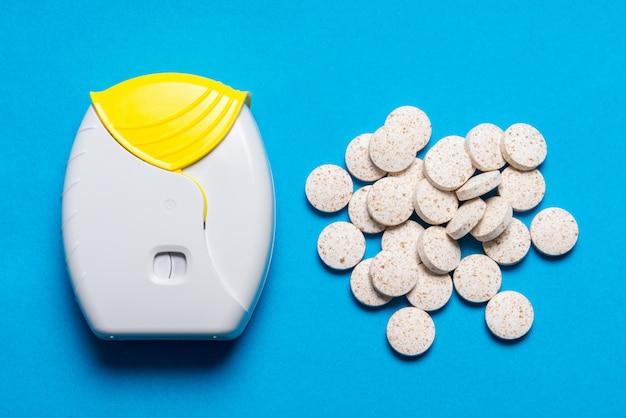 Ингалятор и таблетки на синем фоне
