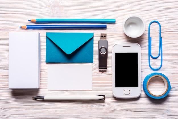青い文房具ツールフラッシュドライブ、ギフトボックス、ビジネスカード、スマートフォン、木製の背景の封筒