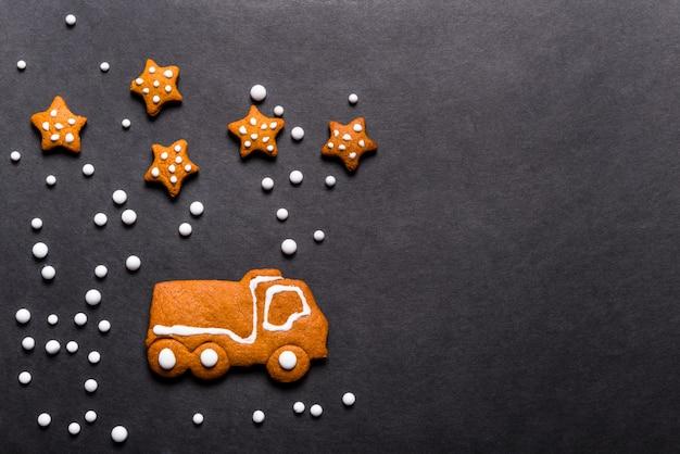 黒の背景、クリスマスコンセプトの形をしたジンジャーブレッドクッキートラック