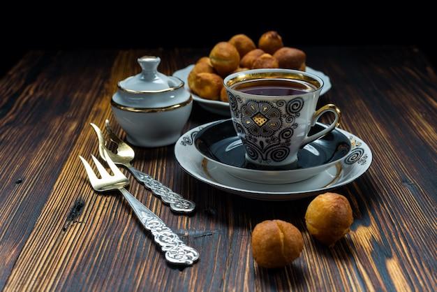 一杯のお茶と木製のテーブルにドーナツ