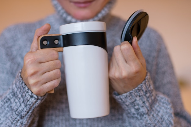 サーモストラベルマグ、白いタンブラーカップ、女性の手でお茶やコーヒーのフラスコ