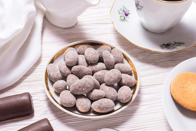木製のテーブルの上の磁器プレートのチョコレート菓子のアーモンド