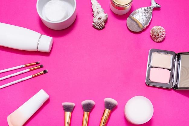 Много макияжа на розовом фоне, копия пространства