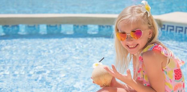 Милая маленькая девочка в бассейне, пить сок