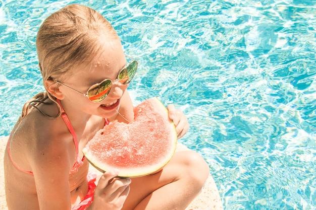 Милая маленькая девочка в бассейне, летних каникулах.
